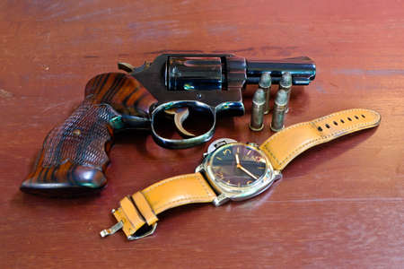Revolver with bullets on brown wooden tables and watches.