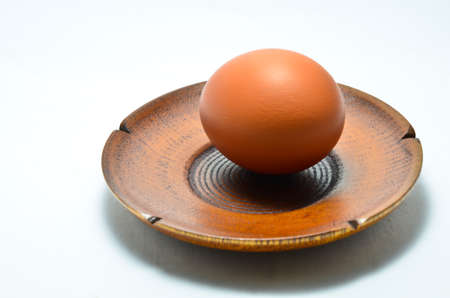eggs in a wood plate placed on a white background. Stock Photo