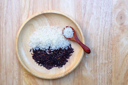 Organic Riceberry Rice and white rice on wood plate and spoon  (black jasmine rice)