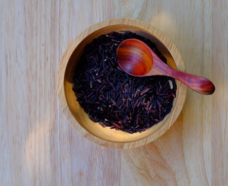 carbohydrates: Organic Riceberry Rice on wood cup and spoon  (black jasmine rice)