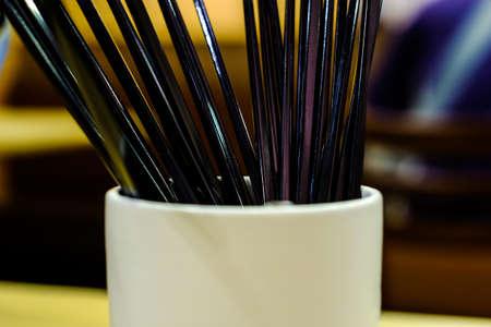 Bundle of black chopsticks in a plastic jar (restaurant) Stock Photo