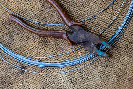 corroded: barbed wire and old cutter on hemp sack. Stock Photo