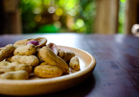 sheath: Stack of boiled peanuts peanuts on wood plate for sale