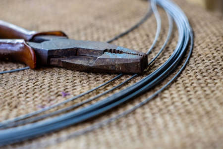 scraped: barbed wire and old cutter on hemp sack. Stock Photo