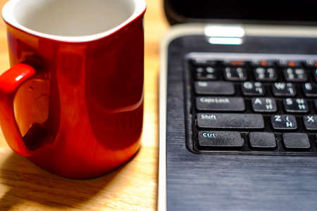 keyboard: Desk table with laptop, coffee cup,  on wooden table. Workplace