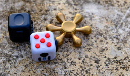 Fidget Cube stress reliever, fingers toy on background, spinner(relax)