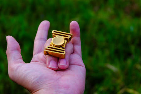 reliever: fidget spinner on hand with love. (Brass fidget spinner) Stock Photo