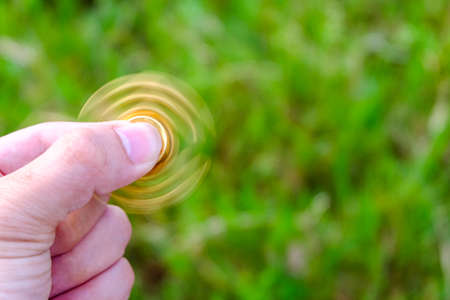 reliever: closeup of a young caucasian man playing with a brass fidget spinner, on nature background