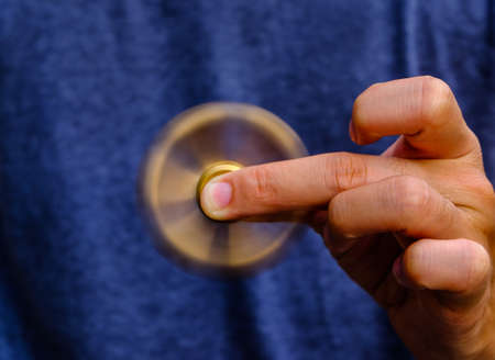 roller: closeup of a young caucasian man playing with a brass fidget spinner.