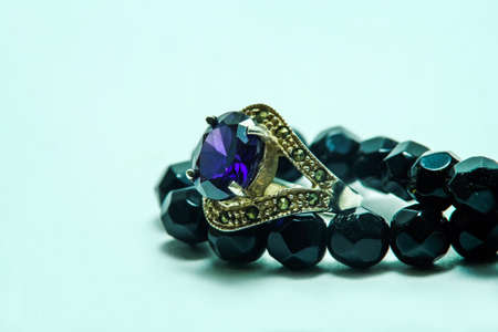 zafiro: Sapphire ring with onyx bead necklace on white background