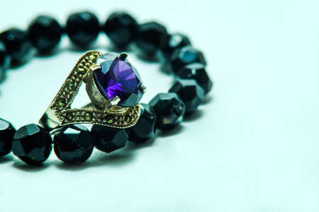 onyx: Sapphire ring with onyx bead necklace on white background