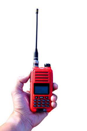 Portable radio transceiver in hand, nature on background