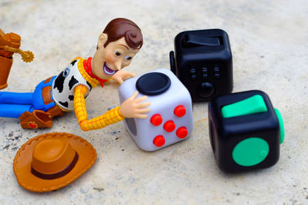 Songkhla, Thailand - July 3, 2017: Woody playing Fidget Cube stress reliever, Fingers Toy (Relax) Editorial