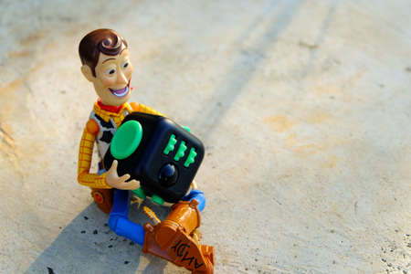 Songkhla, Thailand - June 20, 2017: Woody playing Fidget Cube stress reliever, Fingers Toy (Relax) Editorial