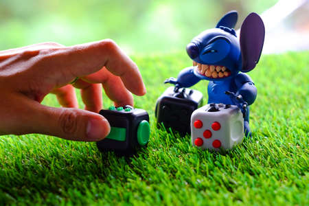 Songkhla, Thailand - July 19, 2017: Stitch playing Fidget Cube stress reliever, Fingers Toy (Pride)