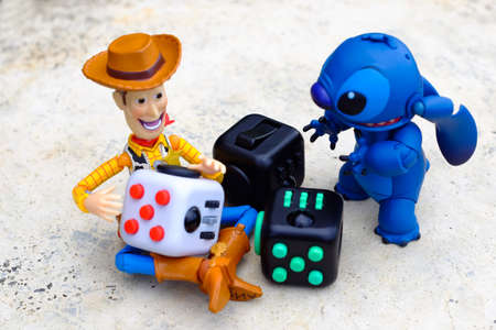 Songkhla, Thailand - July 3, 2017: Woody and stitch playing Fidget Cube stress reliever, Fingers Toy (Relax)