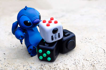 Songkhla, Thailand - July 3, 2017: Stitch playing Fidget Cube stress reliever, Fingers Toy (Relax) Editorial