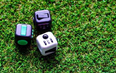 Fidget Cube stress reliever, fingers toy on grass background. (relax)