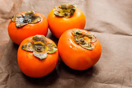 Delicious ripe persimmon fruit on the brown boards