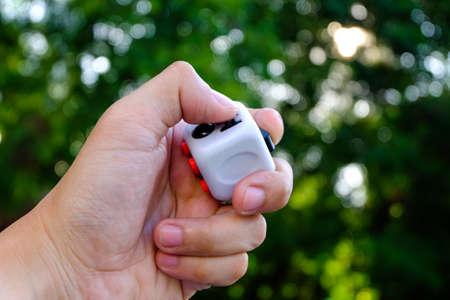 Fidget Cube stress reliever, fingers toy in bokeh background, white. (relax) Stock Photo