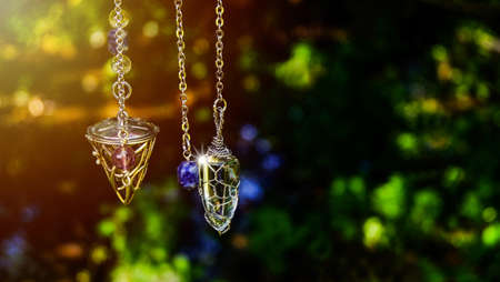 Foretelling the future with crystal pendulum. holding and using quartz crystal pendulum and using it, nature background.