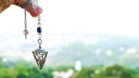 Prédire l'avenir avec un pendule en cristal. tenant et utilisant un pendule en cristal de quartz et l'utilisant, fond de nature.