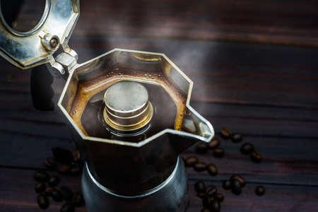 Moka coffee pot on stove. Old style coffee in soft vintage tone. Selective focus. Coffee In A Moka Pot Archivio Fotografico - 133593707