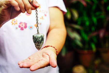 holding and using quartz crystal pendulum and using it In asking questions. Quartz Crystal Pendulum Hanging over a Hand Stockfoto