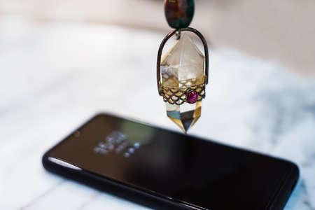 holding and using quartz crystal pendulum and using it In asking questions. pendulum quartz on smart phone background.