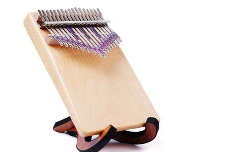 Wooden African instrument Kalimba or mbira is an African musical instrument isolated on white background. Kalimba made from wooden board with metal, play on hands and plucking the tines with the thumbs Stock fotó