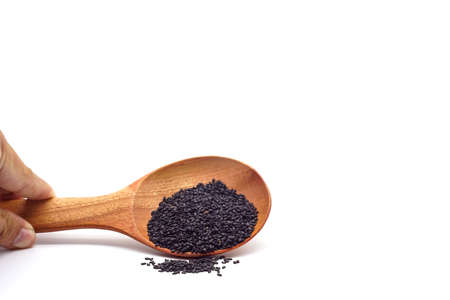 Pile of scattered black sesame seeds with a wooden spoon isolated on white background. Scientific name is Sesamum orientale L.Herb.cereal.