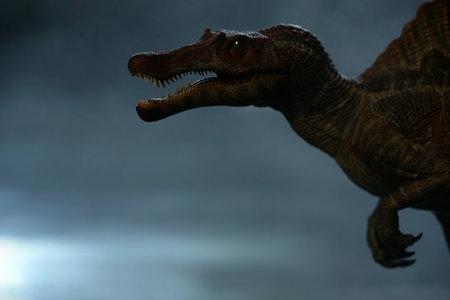 spinosourus dinosaurs toy brown on dark background. closeup dinosaur and monster model. Dinosaur leg organs. Stock Photo