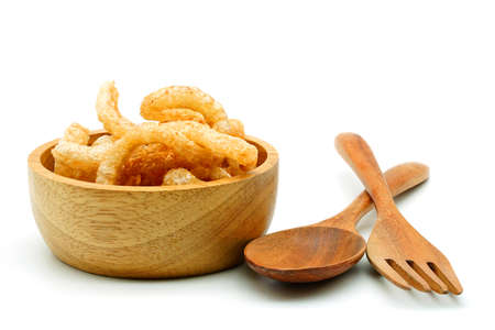 Pork snack or Pork scratching leather lean pork fried crispy and blistered in wood bowl with spoon and fork isoloated on white background. Thai food, Close-up Reklamní fotografie