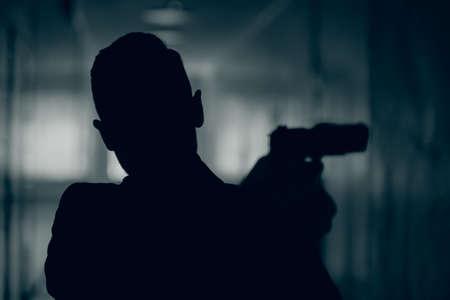 Silhouette of a man with a gun in a dark corridor, close-up. Stockfoto