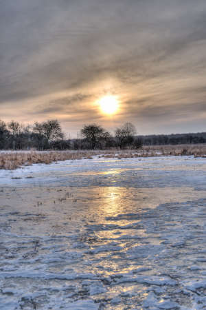 The sun rises over a meadow covered with ice  It is early spring in Denmark  photo