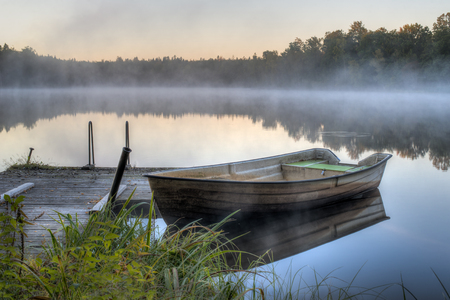 A dirty boat is parked by a wooden pier on a calm lake  It is dawn and soon the sun will be rising