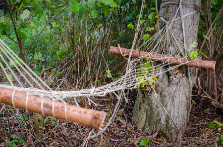 Abandoned hammock made of natural wood found in the forest Stock Photo - 26822598
