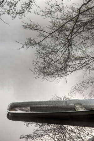 sunk: Water filled boat rear with heavy fog in the background