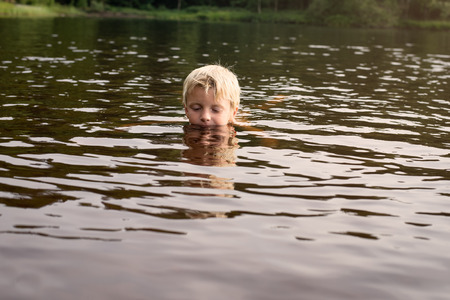 A young boy swimming in a lake late afternoon