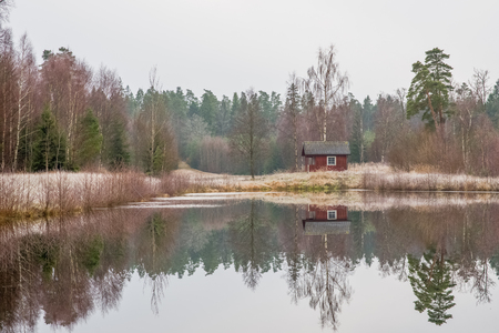 Small Swedish red cottage by a lake  Stock Photo