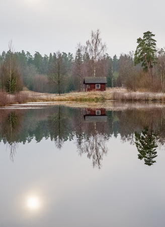 A small cottage by the shore of a small lake with the sun reflected in the calm water Stock Photo