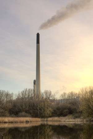 A huge chimney on a power plant is illuminated by the morning sun Stock Photo