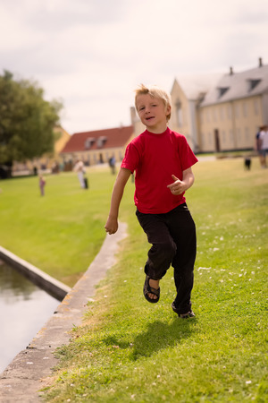 Boy running by water edge in a park with people in the background Stock Photo