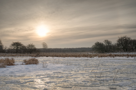 Sunrise over a frozen meadow in early spring.