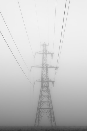 A tall power line tower looms in the fog. Stock Photo