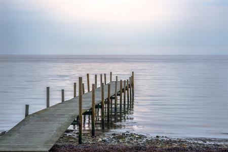 Wooden pier at the beach on a calm morning, with the rising sun shining through a thin cloud layer. Stock Photo