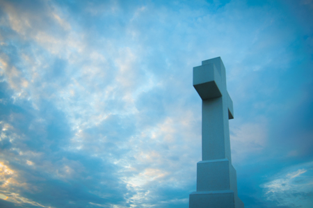 Massive Christian cross in the blue sky made from stone side view