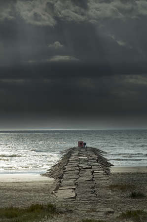 outdoorsman: Fisherman on a stone pier in Galveston, TX on a cloudy early morning