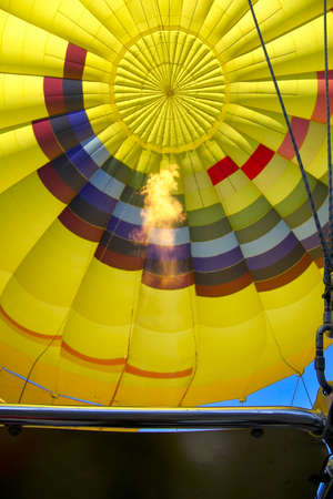 adventure aeronautical: Colorful balloon with a flame heating the air for takeoff Stock Photo