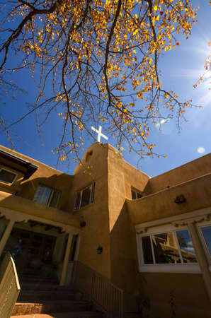 fe: Adobe architecture framed by golden autumn leaves in Santa Fe, New Mexico Stock Photo